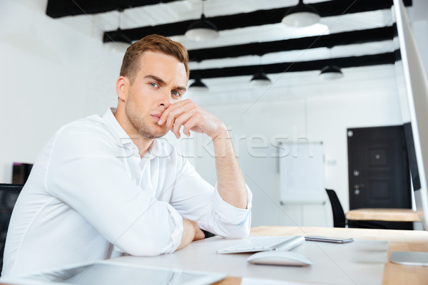 Thoughtful young businessman working with computer in office Stock photo © deandrobot