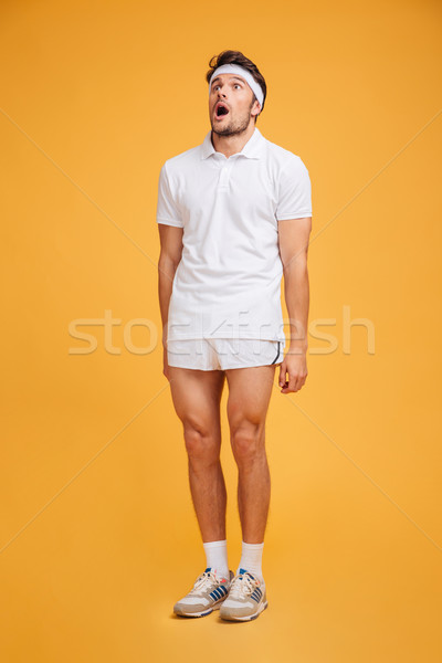 Astonished shocked young man athlete standing with mouth opend Stock photo © deandrobot