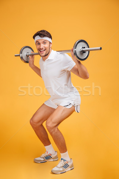 Cheerful young sportsman doing squats with barbell Stock photo © deandrobot