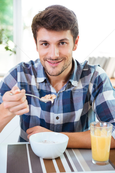 Cheerful man eating cereals with milk for breakfast on kitchen Stock photo © deandrobot