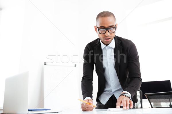üzletember dolgozik néz statisztika papír irat Stock fotó © deandrobot