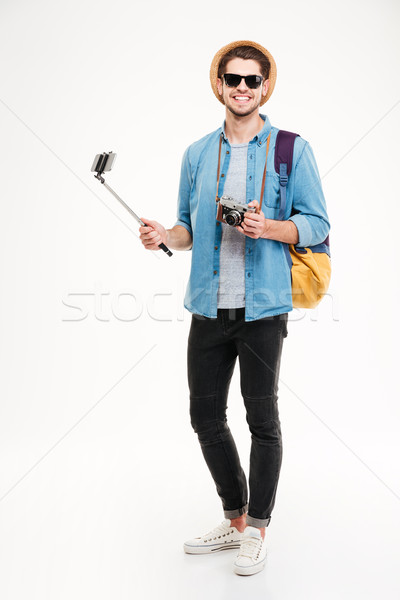Cheerful young tourist, old camera and smartphone on selfie stick Stock photo © deandrobot
