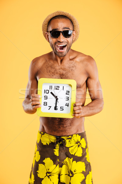 Portrait of a african man in swimwear holding wall clock Stock photo © deandrobot
