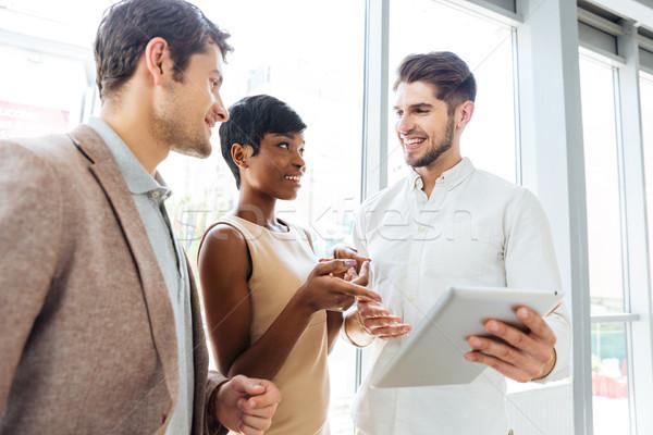 Uomini d'affari parlando tablet insieme ufficio Foto d'archivio © deandrobot