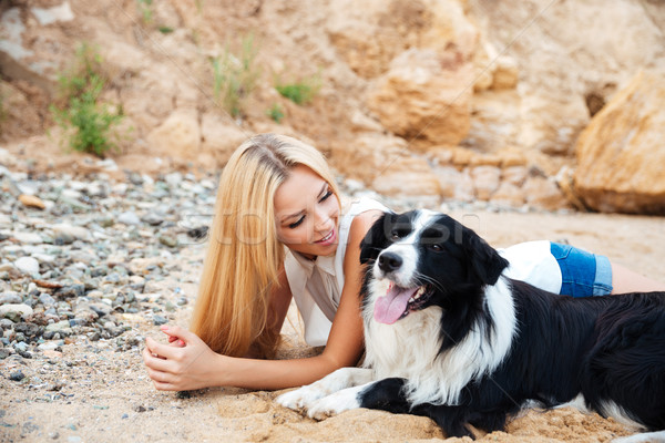 Happy young woman lying with her dog on the beach Stock photo © deandrobot
