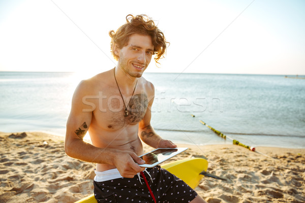 Surfer man using tablet while sitting on the surf board Stock photo © deandrobot