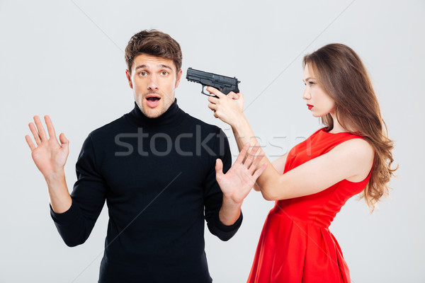 Woman standing and threatening with gun to scared young man Stock photo © deandrobot