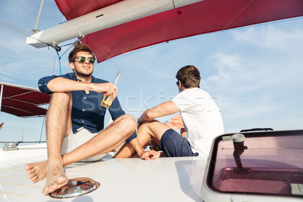 Two men friends drinking beer while resting on the yacht Stock photo © deandrobot