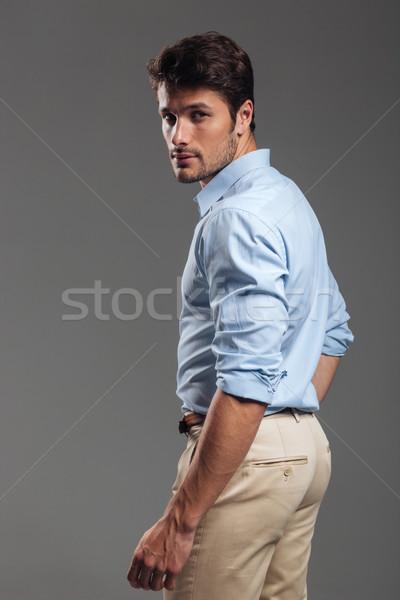 Side view portrait of a pensive man standing Stock photo © deandrobot