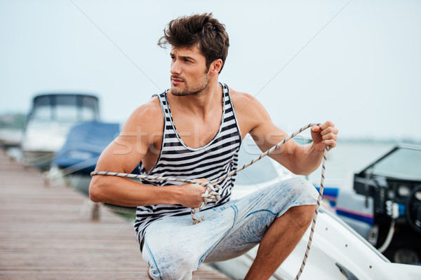 Man preparing boat to start a journe at the pier Stock photo © deandrobot