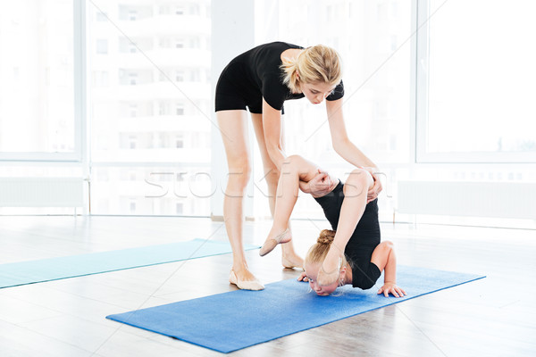 Female dance teacher doing stretching exercises with little gymnast girl Stock photo © deandrobot