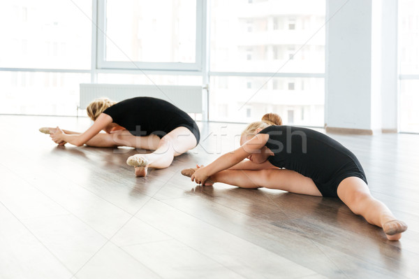 Young attractive ballet teacher and her little student doing exercises Stock photo © deandrobot