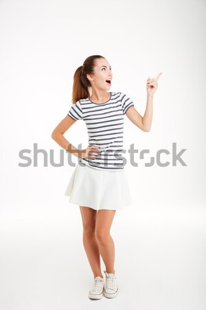 Happy inspired young woman pointing up and having an idea Stock photo © deandrobot