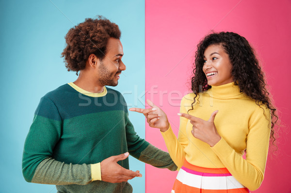 Happy young couple talking and pointing on each other Stock photo © deandrobot