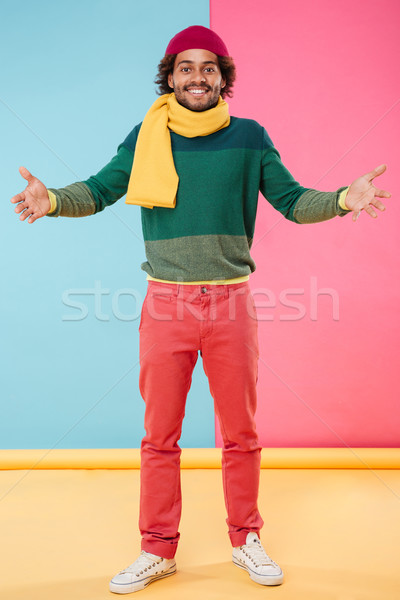 Cheerful african man in hat and scarf showing welcome gesture Stock photo © deandrobot