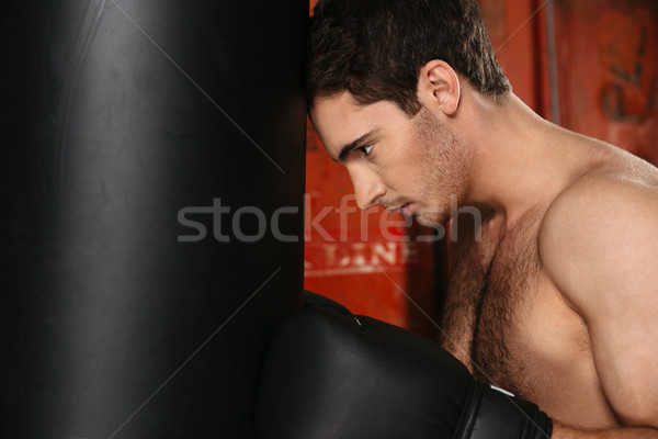Image of tired boxer standing with punchbag Stock photo © deandrobot
