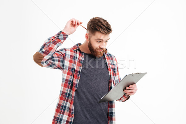 Thoughtful man in plaid shirt scratching his head by hand Stock photo © deandrobot