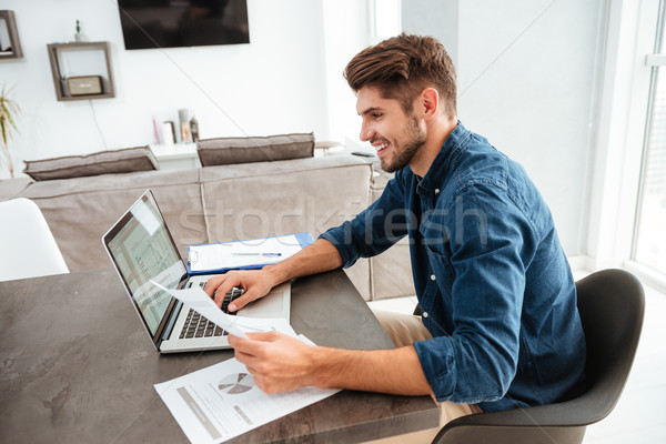 Happy young man analyzing his home finances Stock photo © deandrobot