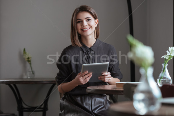 Beautiful lady sitting near window while using tablet computer. Stock photo © deandrobot