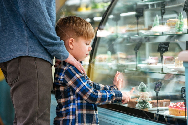 Cute little boy and his father choosing cake in showcase Stock photo © deandrobot