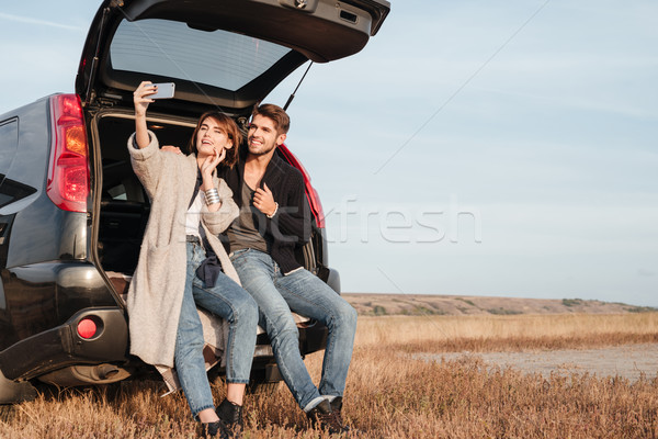 Couple making selfie while sitting inside car at the seaside Stock photo © deandrobot