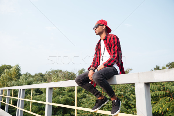 Attractive dark skinned young boy sitting against nature background Stock photo © deandrobot