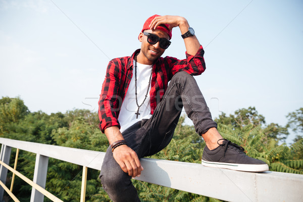 Cheerful dark skinned guy sitting against nature background Stock photo © deandrobot