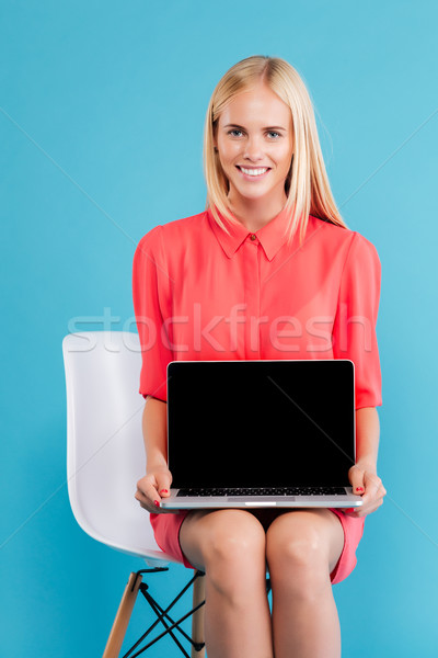Portrait of a cheerful woman sitting with black screen laptop Stock photo © deandrobot