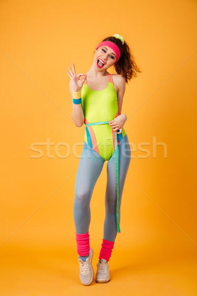 Woman athlete measuring waist with tape and showing ok sign Stock photo © deandrobot