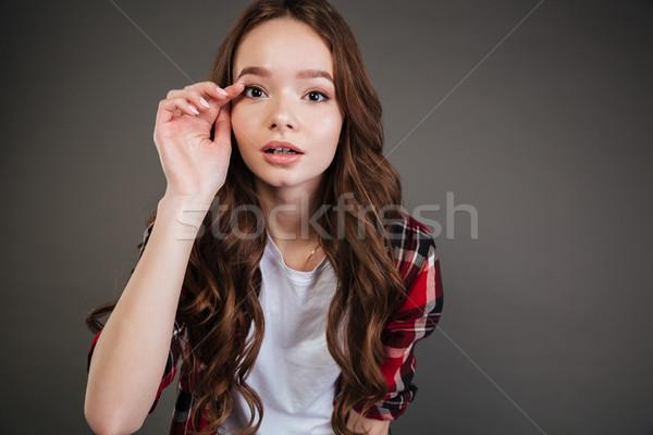 Koncentrált csinos fiatal nő áll megérint szempilla Stock fotó © deandrobot