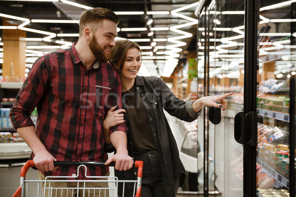 Young cheerful loving couple standing in supermarket choosing the products. Stock photo © deandrobot