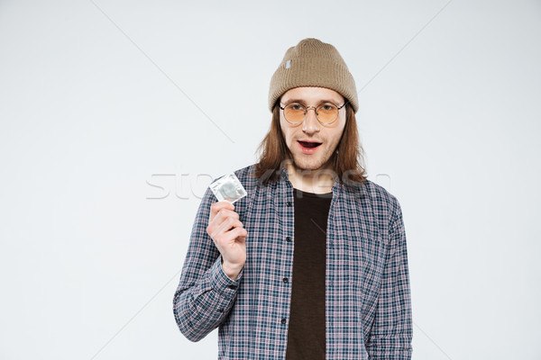 Young hipster holding condom Stock photo © deandrobot