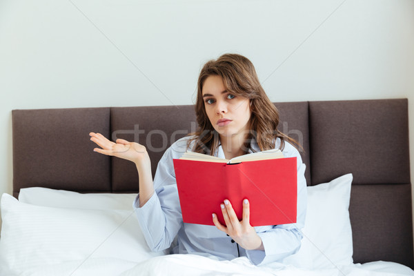 Confused young woman wearing pajamas and holding book in bed Stock photo © deandrobot