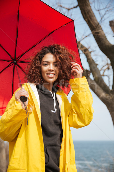 Cheerful african curly young lady wearing yellow coat holding um Stock photo © deandrobot