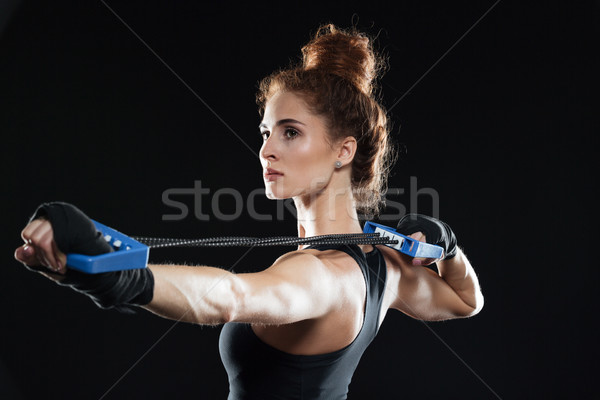 Side view of female fighter using expander Stock photo © deandrobot