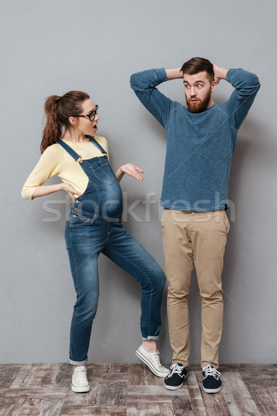 Pregnant serious woman looking at confused man. Stock photo © deandrobot