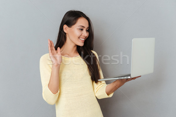 Cheerful charming young woman holding laptop and having video conference Stock photo © deandrobot