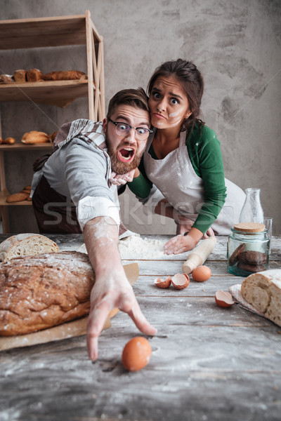 Young man and woman trying to catch egg Stock photo © deandrobot