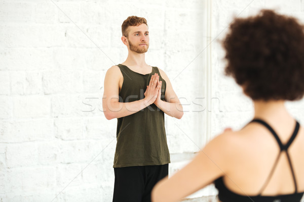 Male yoga instructor practising yoga with group of women Stock photo © deandrobot
