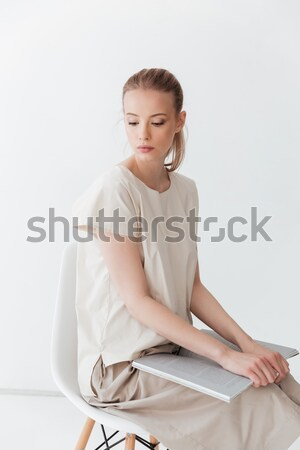 Concentrated blonde lady sitting indoors reading book. Stock photo © deandrobot