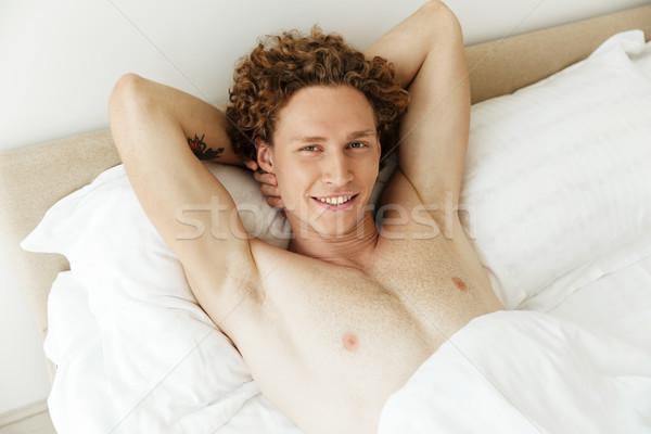 Feliz homem mentiras cama casa quadro Foto stock © deandrobot