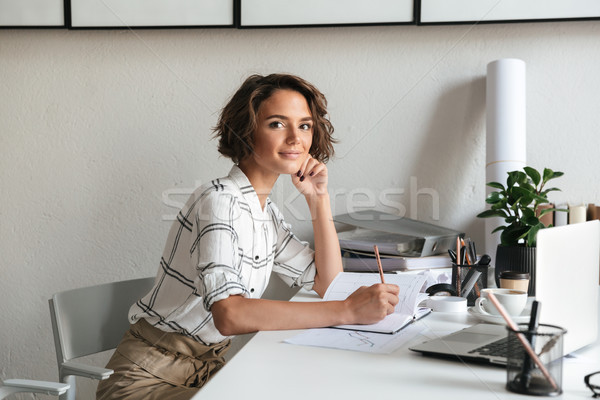 Side view of awesome woman sitting by the table Stock photo © deandrobot