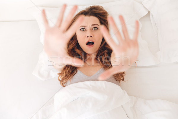 Top view of shocked young woman lying in bed Stock photo © deandrobot