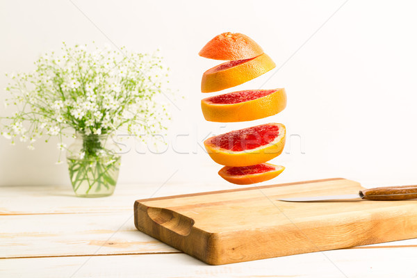 Sliced whole grapefruit flying above a wooden chopping board Stock photo © deandrobot
