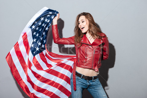Excited happy woman in red leather jacket holding USA flag Stock photo © deandrobot
