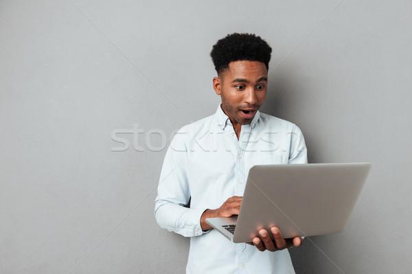 Podniecony afro amerykański człowiek patrząc laptop Zdjęcia stock © deandrobot