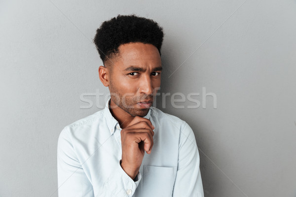 Young pensive african man looking closely at camera Stock photo © deandrobot