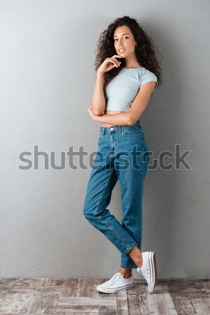 Bella donna guardando fotocamera seriamente isolato i capelli ricci Foto d'archivio © deandrobot