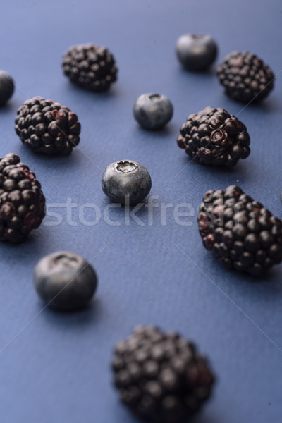Blueberries and mulberries isolated over blue background table. Stock photo © deandrobot