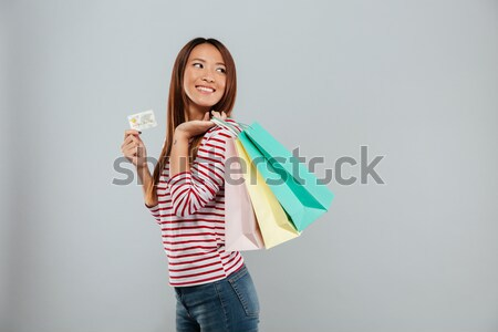 Side view of happy asian woman holding credit card Stock photo © deandrobot